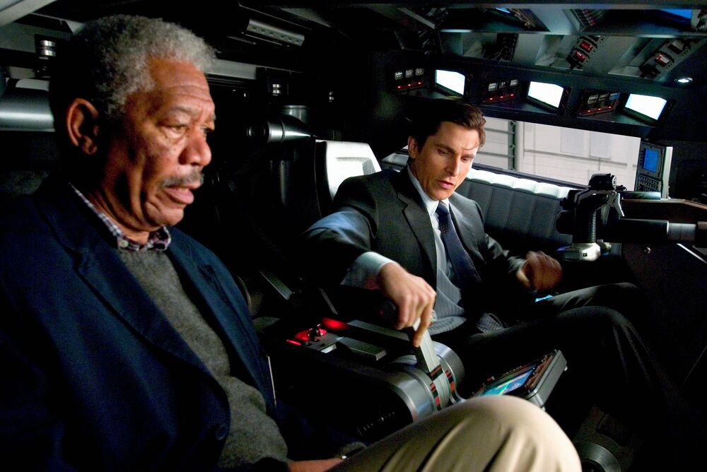 Morgan Freeman and Christian Bale, sitting inside the Batmobile
